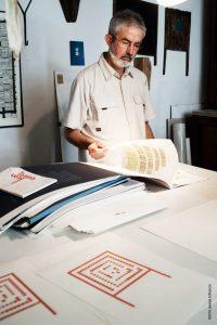 Lucio Passerini mentre sfoglia alcune sue edizioni d'arte