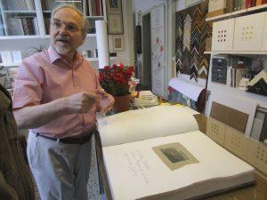 Josef Weiss nel suo atelier a Mendrisio, mentre mostra una delle sue preziose edizioni